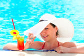 Happy girl with a cocktail at the pool holding a hat hand — Stock Photo