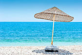 Lone wicker umbrella on the beach — Stock Photo