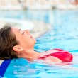 Beautiful girl relaxes in the pool with your eyes closed — Stock Photo #27894651