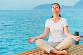 Girl sitting on a pier in the lotus position — Stock Photo