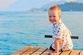 Happy little boy sitting on a pier — Stock Photo