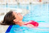 Красивая девушка отдыхает в бассейне с закрытыми глазами — Стоковое фото