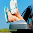 Female legs dangling from open car window in shales — Stock Photo #28294541