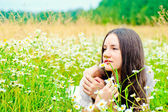 Girl resting in a field of chamomile — Stock Photo