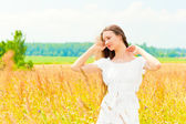 Beautiful young Russian girl in a field with gold ears of wheat — Stock Photo