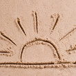 The sun sets over the horizon at sea drawing in the sand — Stock Photo