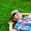 Happy little boy lying down resting on the green grass in sunglasses — Stock Photo