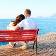 Love couple sitting on a bench by the sea embracing — Stock Photo