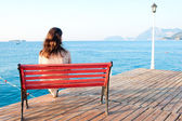 Girl sitting on a bench on the pier at the sea and reflects — Stockfoto