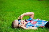 Happy boy resting lying on green grass in sunglasses — Stock Photo