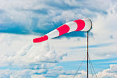 Striped windsock at the airport on the background of beautiful clouds — Stock Photo