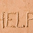 On the wet sand written the word Help! by the sea — Stock Photo