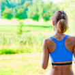 Stockfoto: Sports girl runs in morning in park, rear view