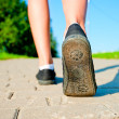 Female legs in sneakers close up running down the road in the morning — Stock Photo