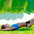 Slim athletic girl has pilates on the grass by the lake in the park — Stock Photo