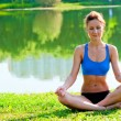 图库照片: Tightened girl in sportswear meditating in lotus position at lake in park