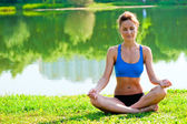 Tightened girl in sportswear meditating in the lotus position at the lake in the park — Stock Photo