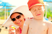 Mom puts on the baby's skin lotion for sun protection — Stock Photo