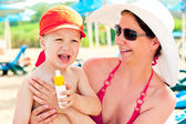 Mom and son on the beach to protect the skin from sun lotion — Stock Photo