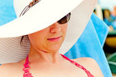 Portrait of a girl in a white hat with a wide brim on the beach — Stock Photo