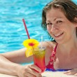 Charming girl in the pool and a glass of alcoholic cocktail — Stock Photo