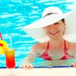 Young girl in a white hat in the swimming pool — Stock Photo