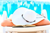 Girl asleep in a lounge chair near the pool with a book — Stock Photo