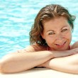 A beautiful young girl at the edge of the pool smiling — Stock Photo