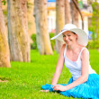Stock Photo: Girl resting on the lawn and laughs gaily