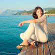 Girl sitting on a pier near the sea and looking to the side — Foto de Stock