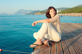Girl sitting on a pier near the sea and looking to the side — Stock Photo