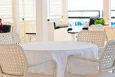 In de cafetaria rieten stoelen en tafels bedekt met doek — Stockfoto