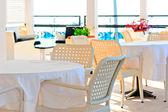 表覆盖着白色的桌布和柳条椅子 — 图库照片