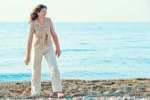 Cheerful woman walking along the beach barefoot — Stock Photo