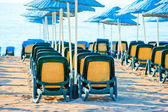 Chairs stand in a row under blue umbrellas — Stock Photo