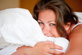 Young woman hugging a pillow in bed — Stock Photo
