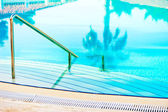 Stairs leading to the blue clear water in the swimming pool — Stock Photo