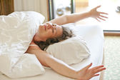 She woke up in the morning in bed and stretches — Stock Photo