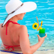 A girl in a white wide-brimmed hat with a cocktail in the pool — Stock Photo