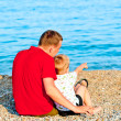Son reveals that his father is in the sea, they are sitting — Stock Photo