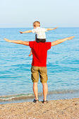 Father and son on the beach portray flight — Stock Photo