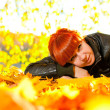 Woman with red hair and yellow leaves around it — Stock Photo
