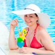 Girl in the pool with a cocktail smiles — Stock Photo