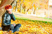 Girl sitting in maple autumn sunny day — Stock Photo