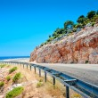 Stock Photo: Highway guardrail in mountains and beautiful rock