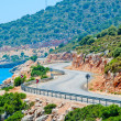Stock Photo: Winding road in mountains leads to sea
