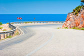 Mountain highway leading to the sea — Stock Photo