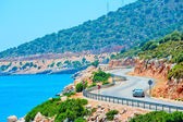 Car driving on mountain road along the sea — Stock Photo