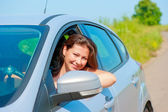 Female driver looks out the car window — Stock Photo