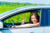 Smiling girl driving a car on nature — Stock Photo